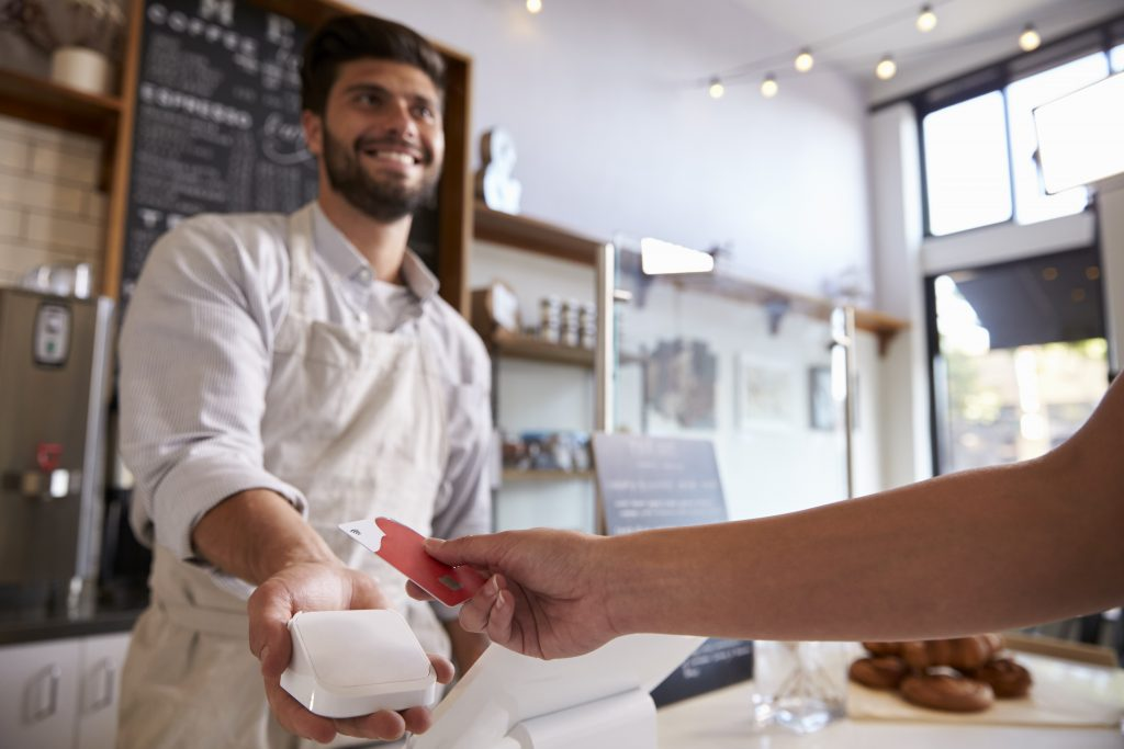 Barista takes credit card payment at a coffee shop