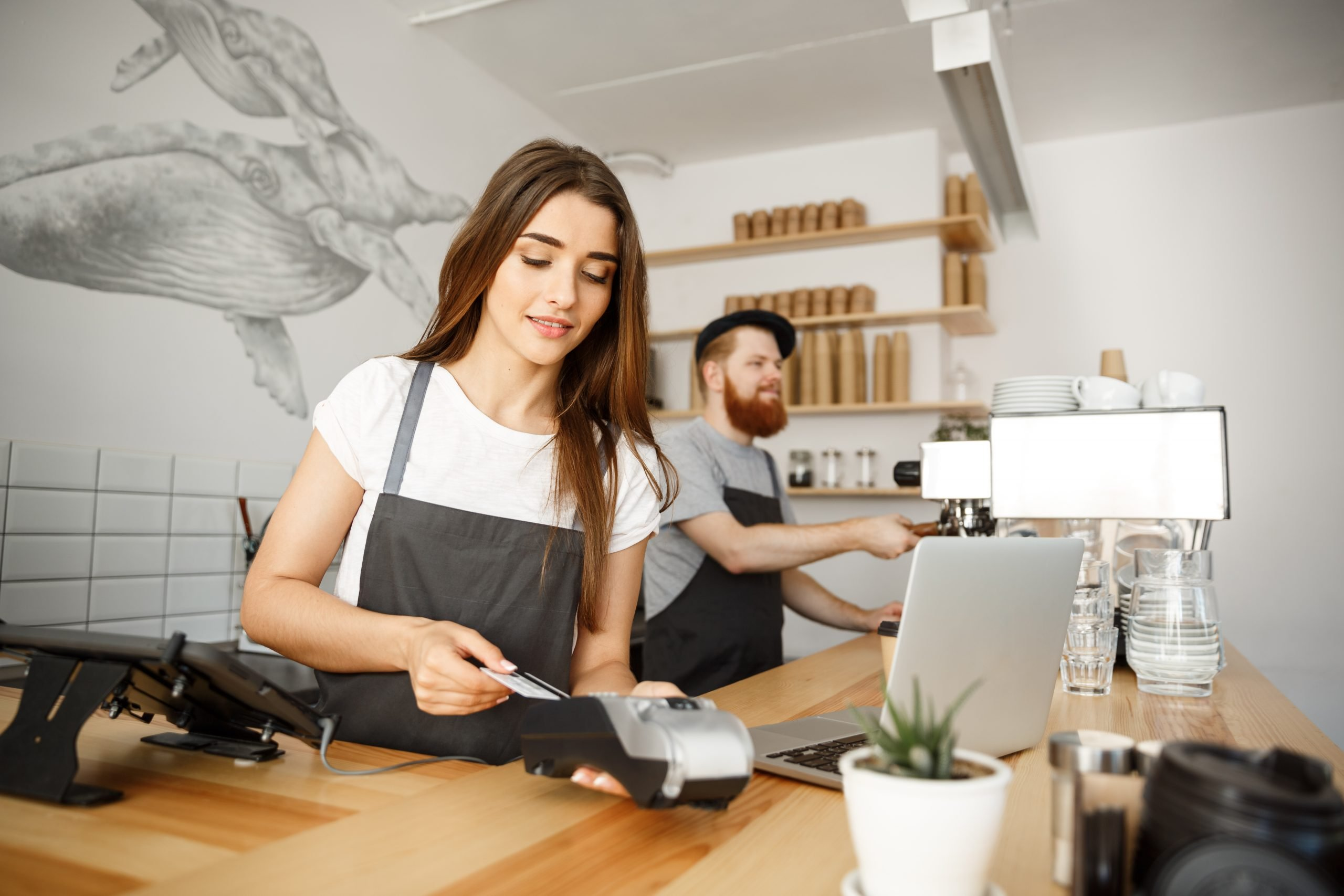 Barista taking credit card payment with a EMV payment terminal