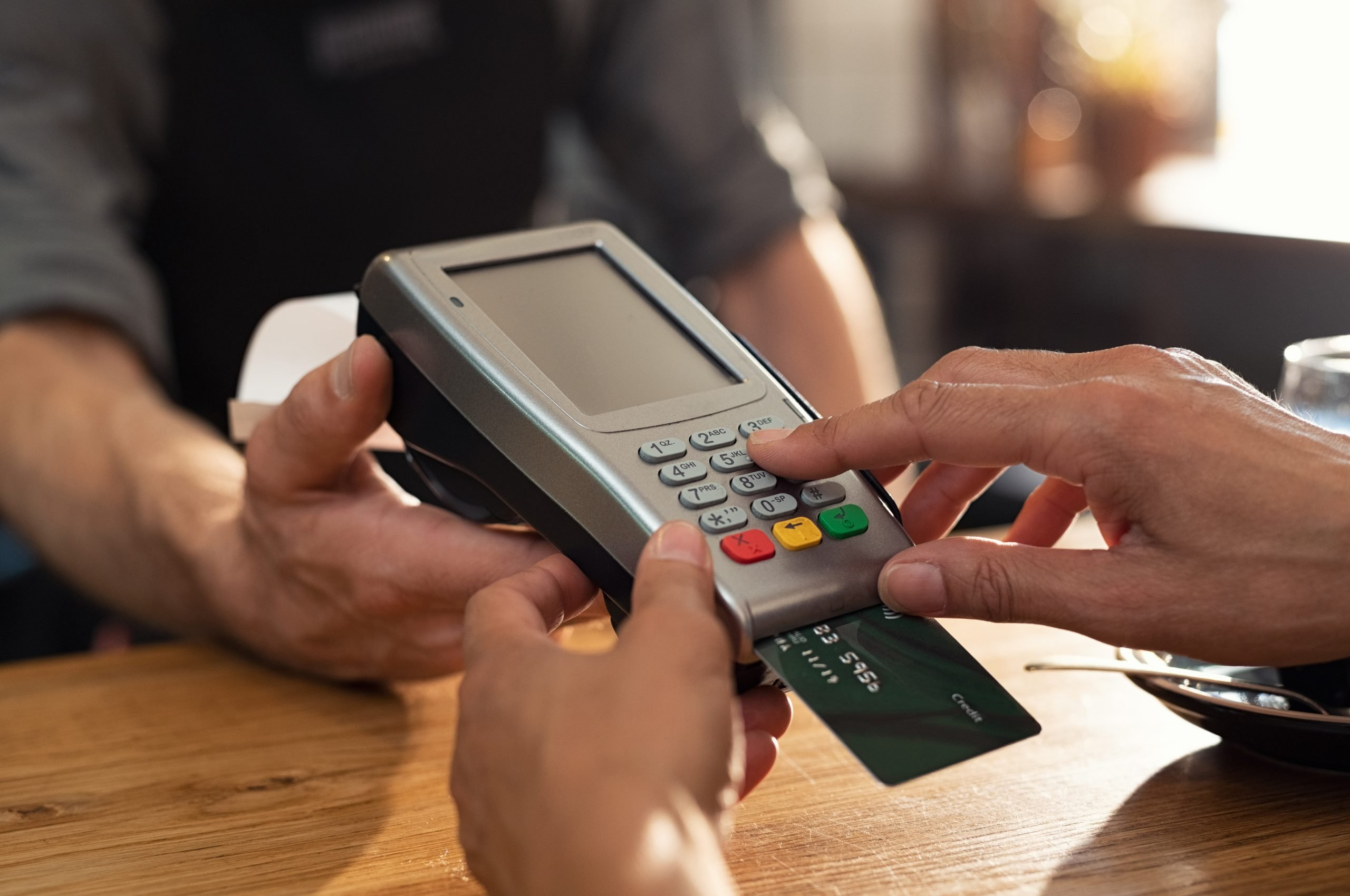 Customer typing in their PIN for a debit card payment