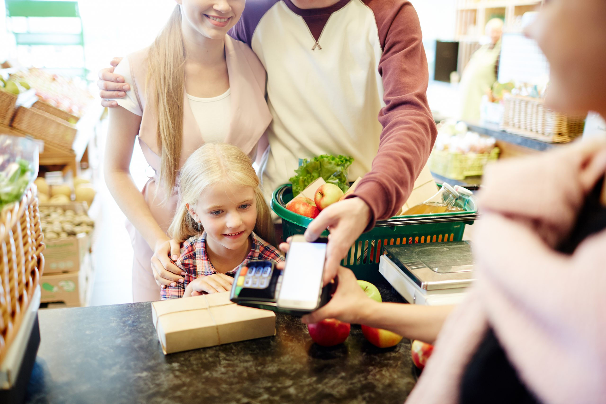 Family using their smartphone to make an NFC payment