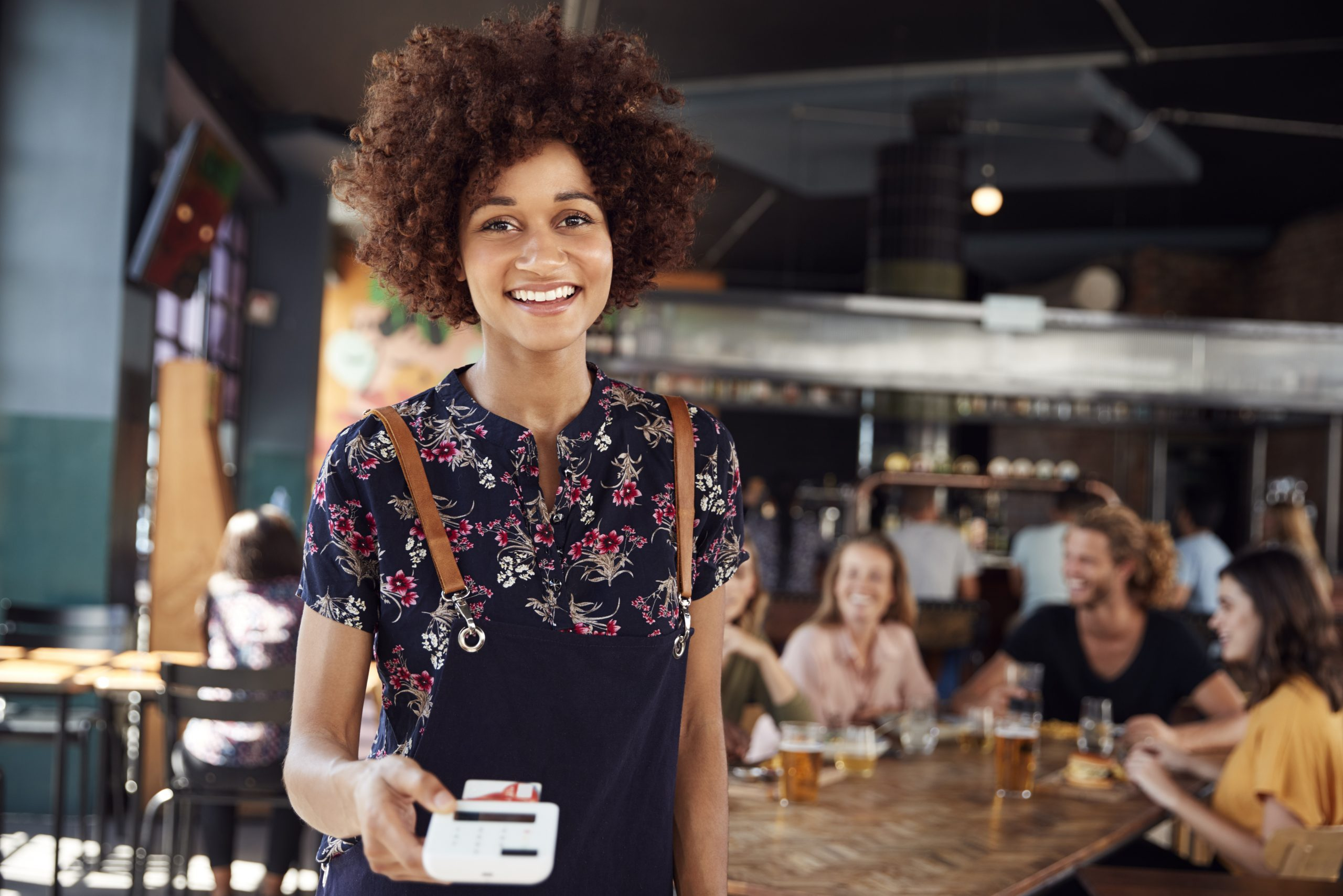Waitress Holding Credit Card Payment Terminal In Busy Bar Restaurant