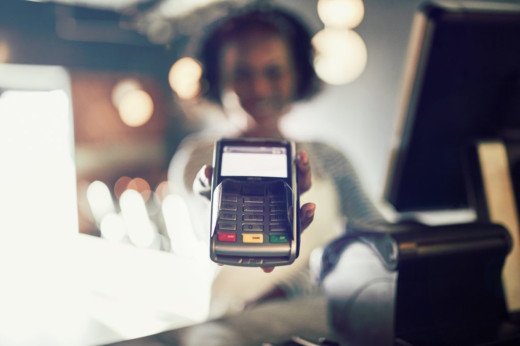 Restaurant waitress holding credit card terminal