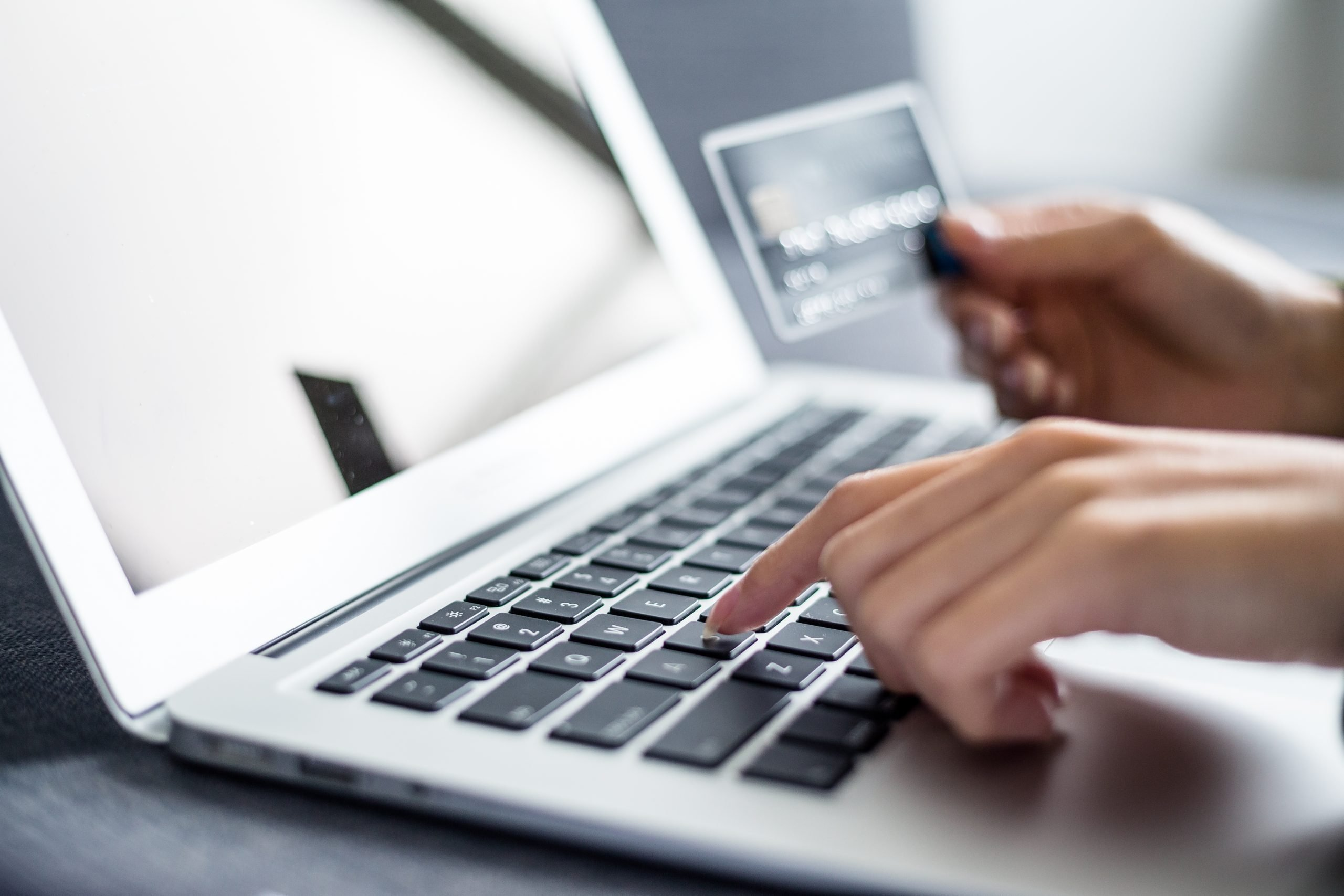 Woman holding credit card and using computer for online shopping