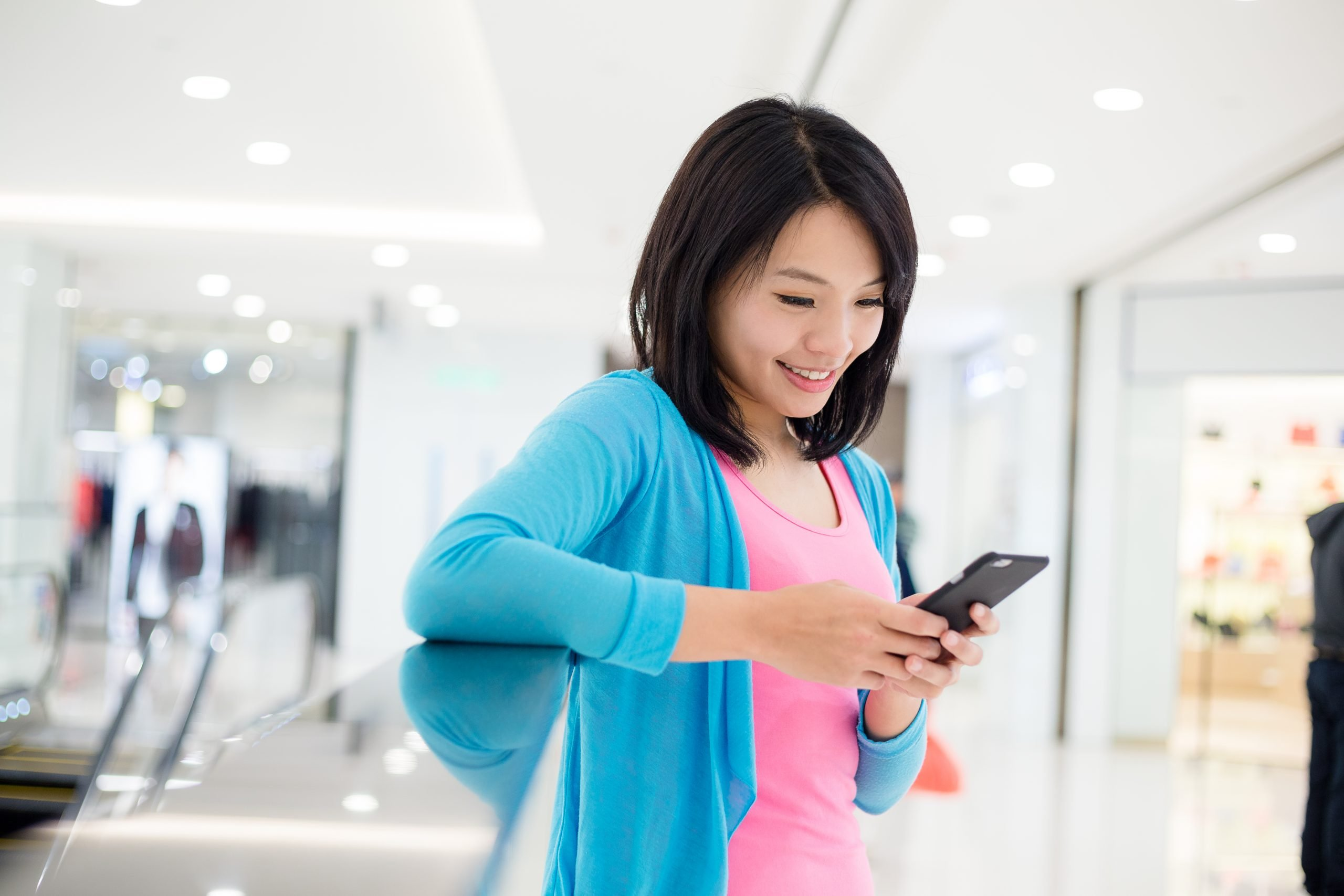 Woman using cellphone inside department store