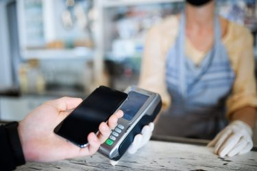 Contactless payment with smartphone, coffee shop open after lockdown