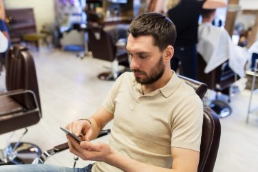 Manager checking a salons sales through his smartphone